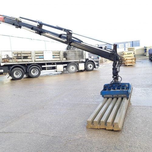 Grabber unloading concrete beams from rigid