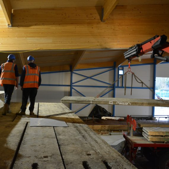 indoor crane lifting hollowcore planks into position