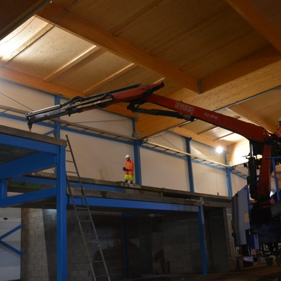 indoor commercial crane assisting to lift planks for second floor
