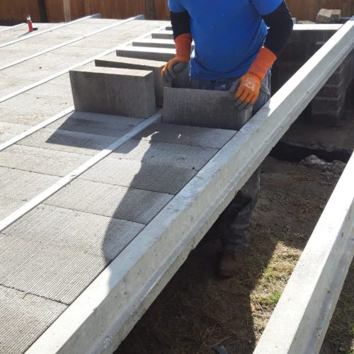 groundworker installing blocks in between beams previously laid