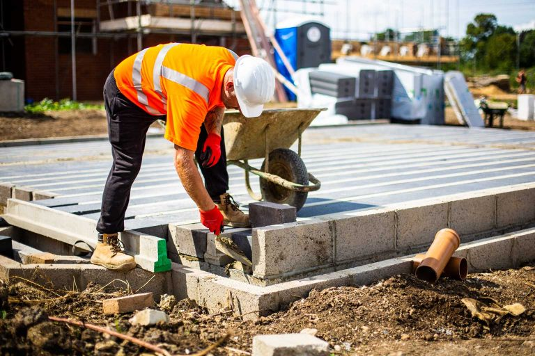 worker cementing block at the end of site