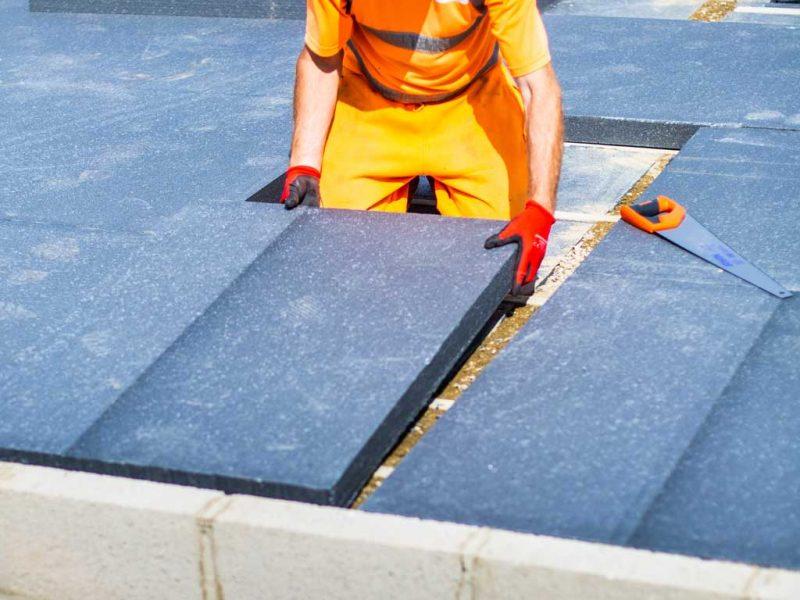Workman Installing Insulated Concrete Floor Top Sheet