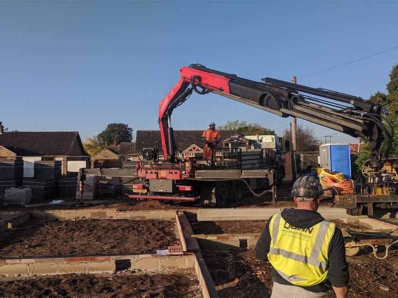Crane being used to move standard beams