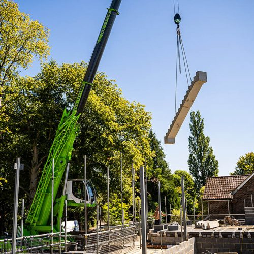 Crane holding precast concrete stairs with trees in background