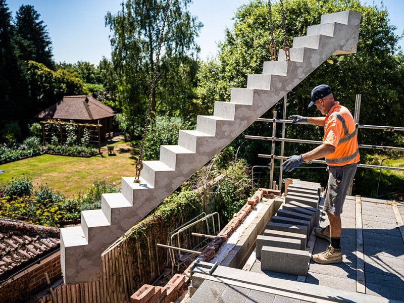 Installer guiding precast concrete stairs into place from crane