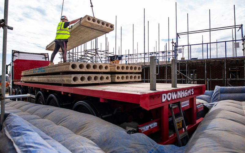 Red lorry with concrete planks being lifted off by worker in hi-vis and hardhat